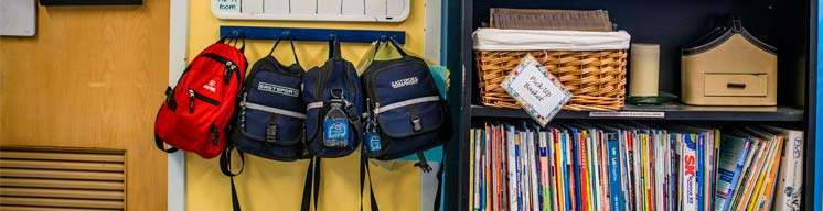 Children's backpacks hanging on wall